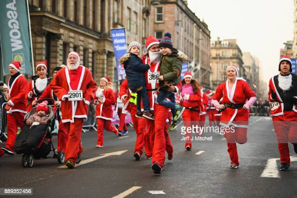 Over eight thousand members of the public take part in Glasgow's annual Santa dash make their way along St Vincent Street on December 10 2017 in...
