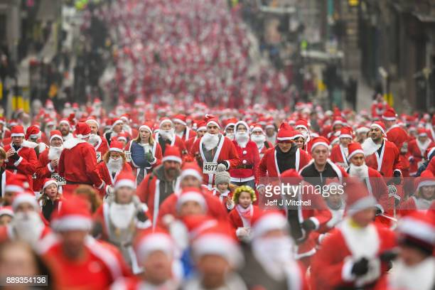 Over eight thousand members of the public take part in Glasgow's annual Santa dash make their way up St Vincent Street on December 10 2017 in Glasgow...