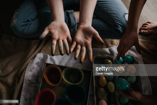 over head shot of children dying chicken eggs - dirty easter stock pictures, royalty-free photos & images