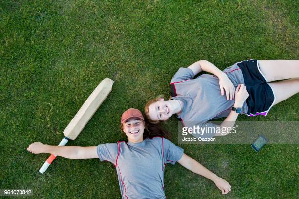 over head shot of two female cricket players lying on grass with sports gear - cricket player stock pictures, royalty-free photos & images