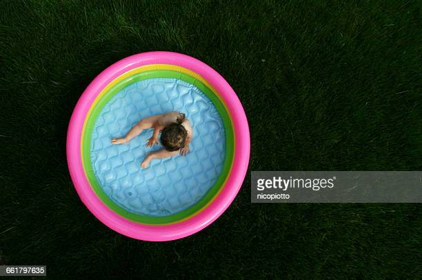 Over head view of girl sitting in paddling pool