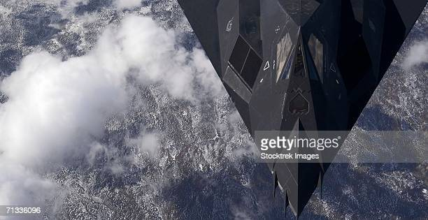 over new mexico - an f-117a nighthawk from holloman air force base, n.m. flies high over the mountains during a training mission. - stealth bomber stock photos and pictures