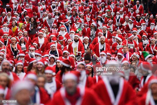 Over seven thousands of members of the public dressed as Santas make their way up St Vincent Street on December 11 2016 in Glasgow Scotland The Santa...