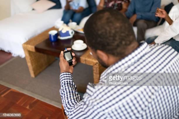 結果を待っている糖尿病のホームテストキットを保持している肩の上の男 - looking over shoulder ストックフォトと画像