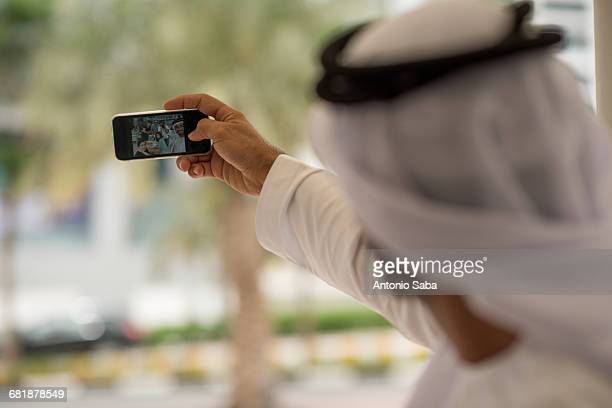 Over shoulder of middle eastern man taking smartphone selfie with friends at cafe, Dubai, United Arab Emirates