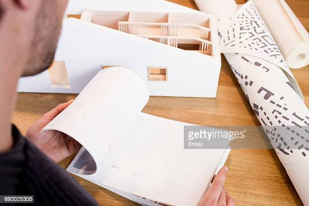 Over shoulder view of architect looking at book