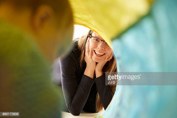 over shoulder view of baby girl crawling in multi-colour tunnel to mother - mama bear stock photos and pictures