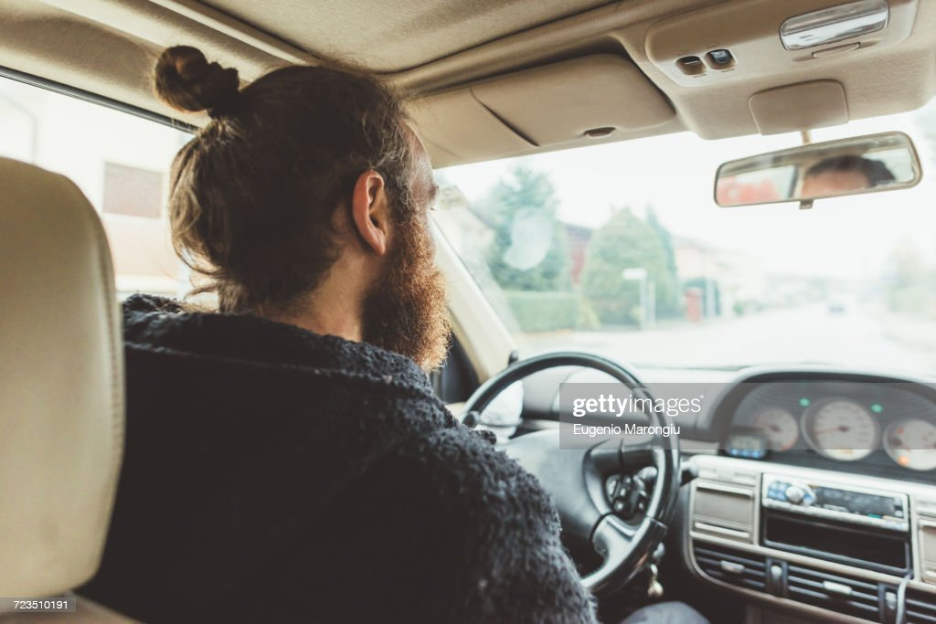 Over shoulder view of bearded man driving a car : Stock Photo