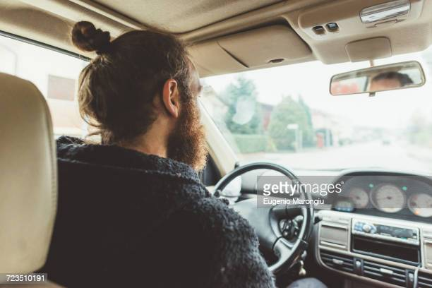 Over shoulder view of bearded man driving a car