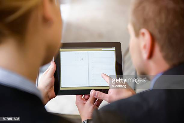 Over shoulder view of businesswoman and man using digital tablet in office