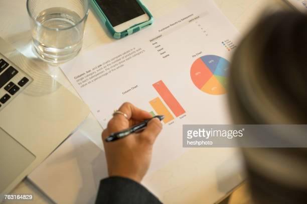over shoulder view of businesswoman looking at piecharts at office desk - heshphoto fotografías e imágenes de stock