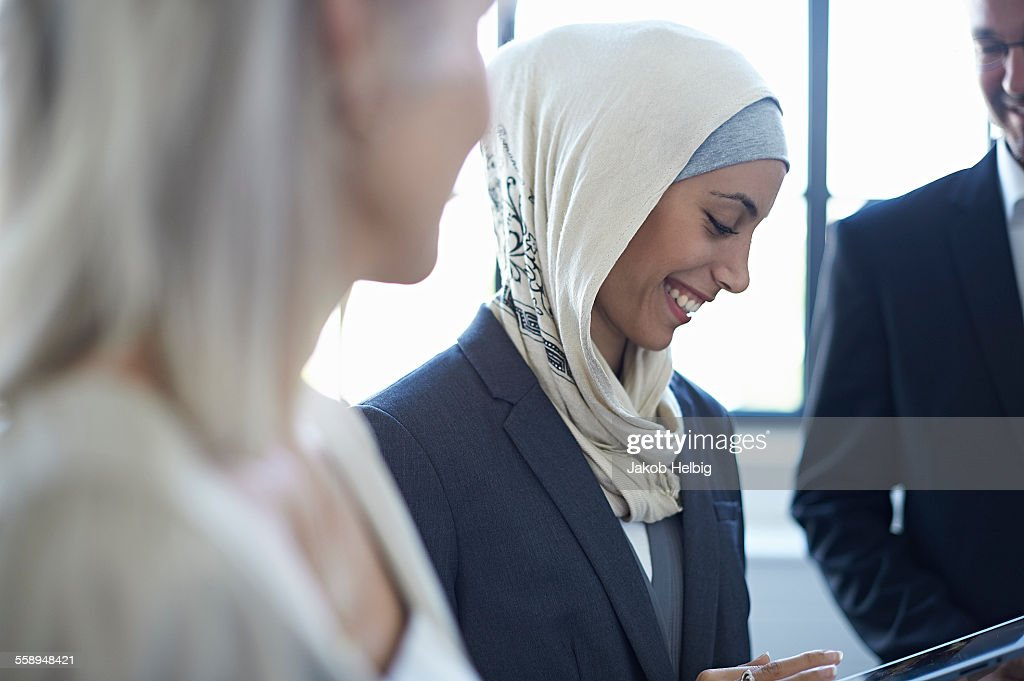 Over shoulder view of businesswomen and man chatting in office : Stock Photo