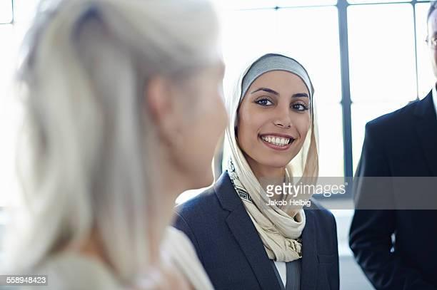 over shoulder view of businesswomen chatting in office - hoofddeksel stockfoto's en -beelden