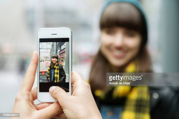 over shoulder view of female hands photographing best friend on smartphone - prendre une photo photos et images de collection