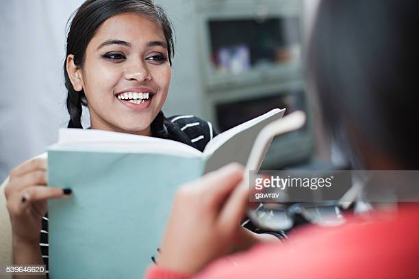 Over shoulder view of happy Indian girl students discussing.