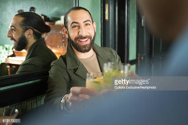 over shoulder view of male friends drinking cocktails in recreational bar - heshphoto stock pictures, royalty-free photos & images
