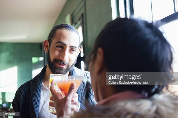 over shoulder view of man flirting with woman at recreational bar - heshphoto stock pictures, royalty-free photos & images