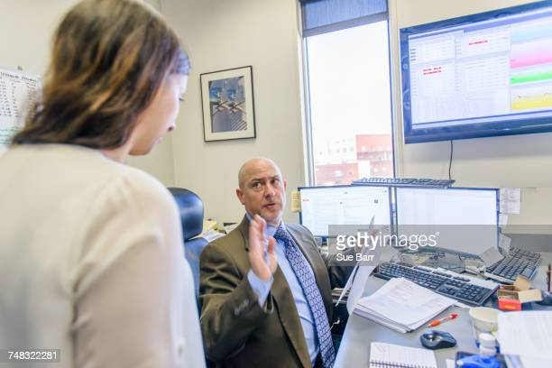 Over shoulder view of manager having discussion with office worker at office desk