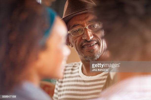 Over shoulder view of mature man chatting to couple, Ipanema beach, Rio De Janeiro, Brazil