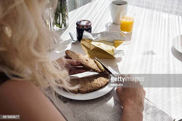 Over shoulder view of mature woman spreading butter onto bread