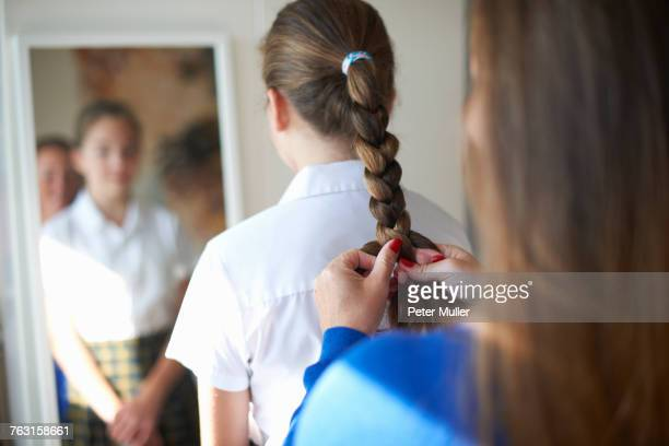 Over shoulder view of mother plaiting teenage schoolgirl daughters hair