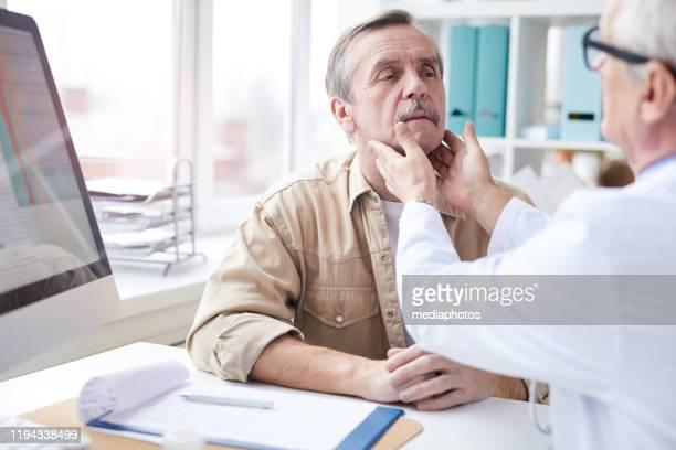 首のしこり検査をしながら、テーブルに座って成熟した男性の首に触れる上級医師の肩越しのビュー - looking over shoulder ストックフォトと画像