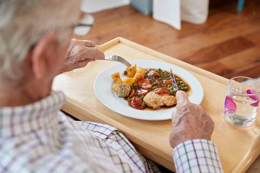 Over shoulder view of senior man eating dinner at home 849305512