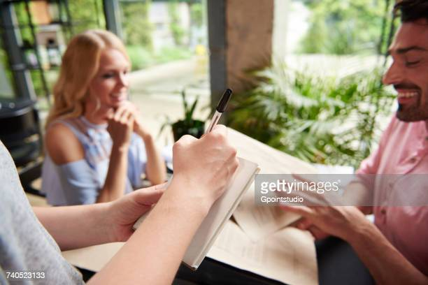 Over shoulder view of waitress writing order from couple at restaurant table