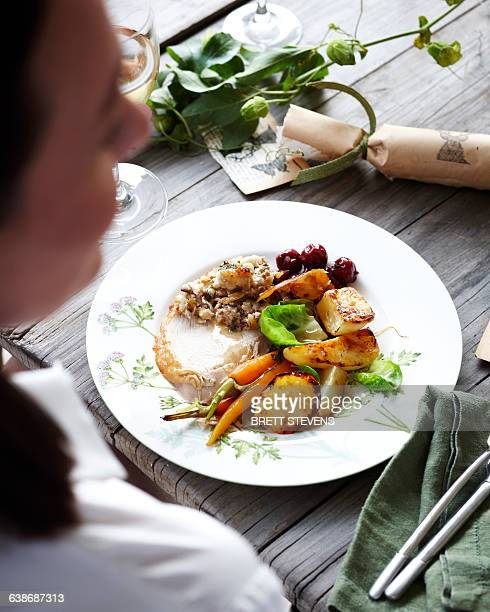 over shoulder view of woman eating christmas dinner - one mid adult woman only stock pictures, royalty-free photos & images
