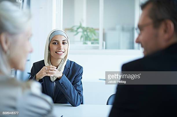 over shoulder view of young businesswoman at interview in office - religious veil stock pictures, royalty-free photos & images