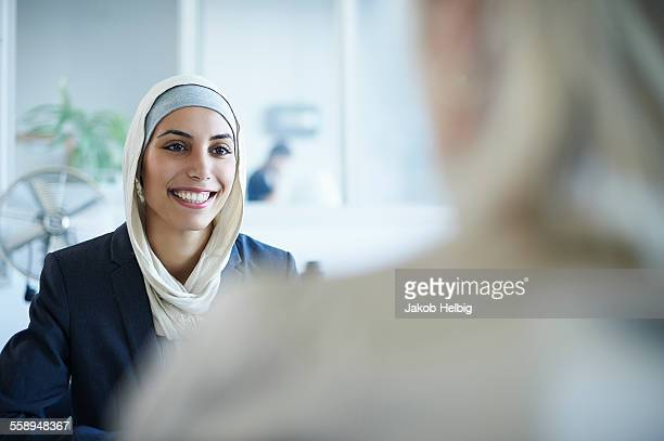 Over shoulder view of young businesswoman chatting to colleague in office