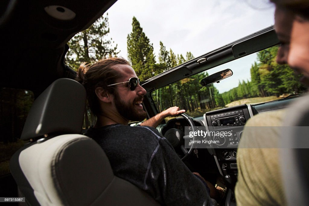 Over shoulder view of young couple driving in jeep : Stock Photo