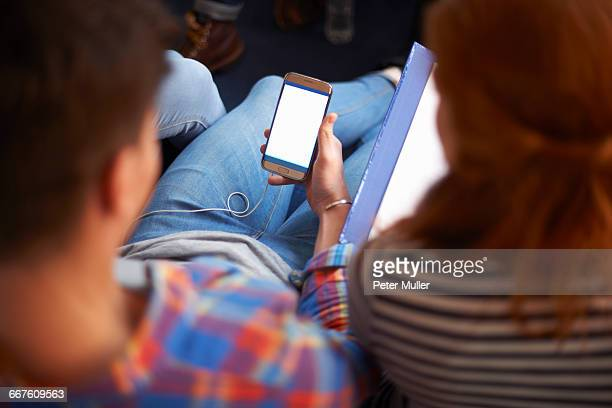 Over shoulder view of young male and female students reading smartphone texts in common room