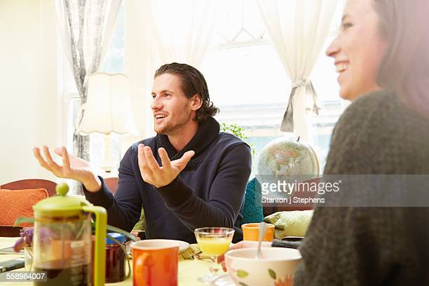 Over shoulder view of young man explaining at breakfast table