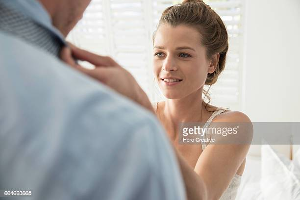 Over shoulder view of young woman fastening boyfriends tie
