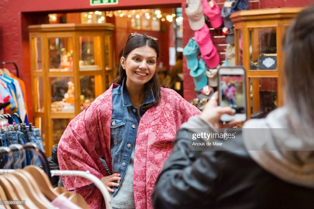 Over shoulder view of young woman photographing friend in pink kimono at vintage market stall : Stock-Foto