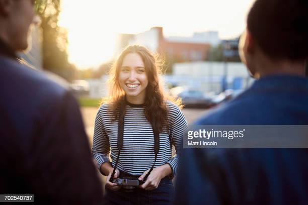 Over shoulder view of young woman talking to male friends on sunlit street