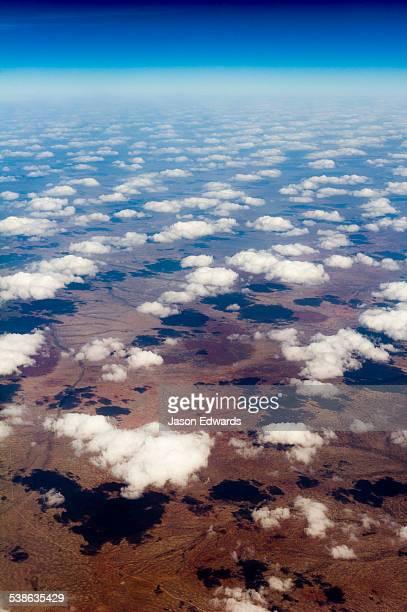 A flotilla of white fluffy clouds casting shadows onto a vast desert plain.
