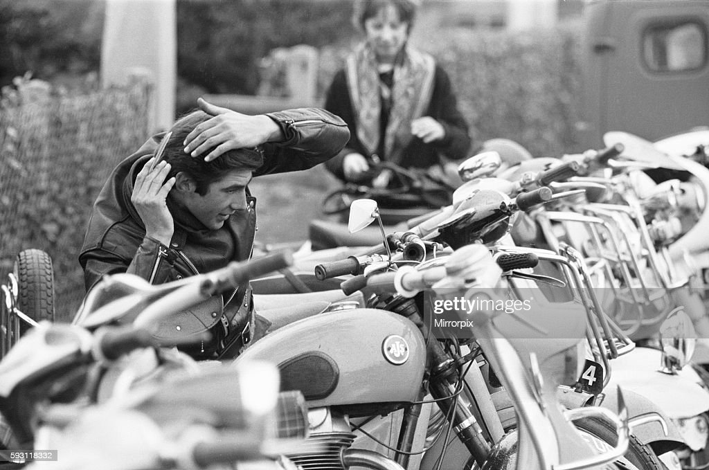 Rocker combs his hair using the mirror of a mods scooter on Clacton sea front. : News Photo
