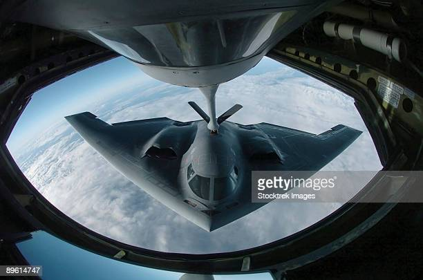 over the pacific ocean - a b-2 spirit bomber refuels from a kc-135 stratotanker here during a deployment to andersen air force base, guam.   - stealth bomber stock photos and pictures