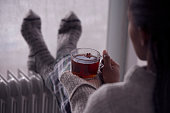 Over the shoulder image of a woman drinking tea at home in cold and wet weather.