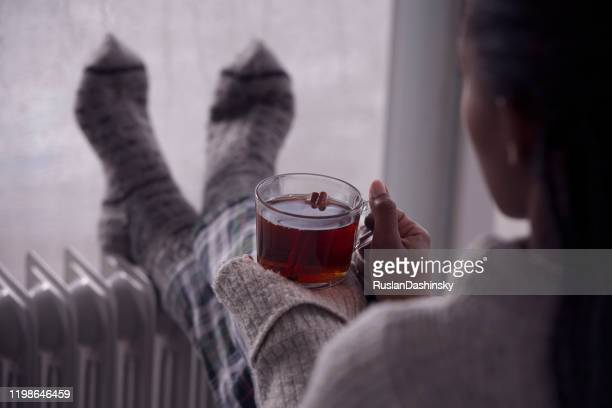 over the shoulder image of a woman drinking tea at home in cold and wet weather. - tea hot drink stock pictures, royalty-free photos & images