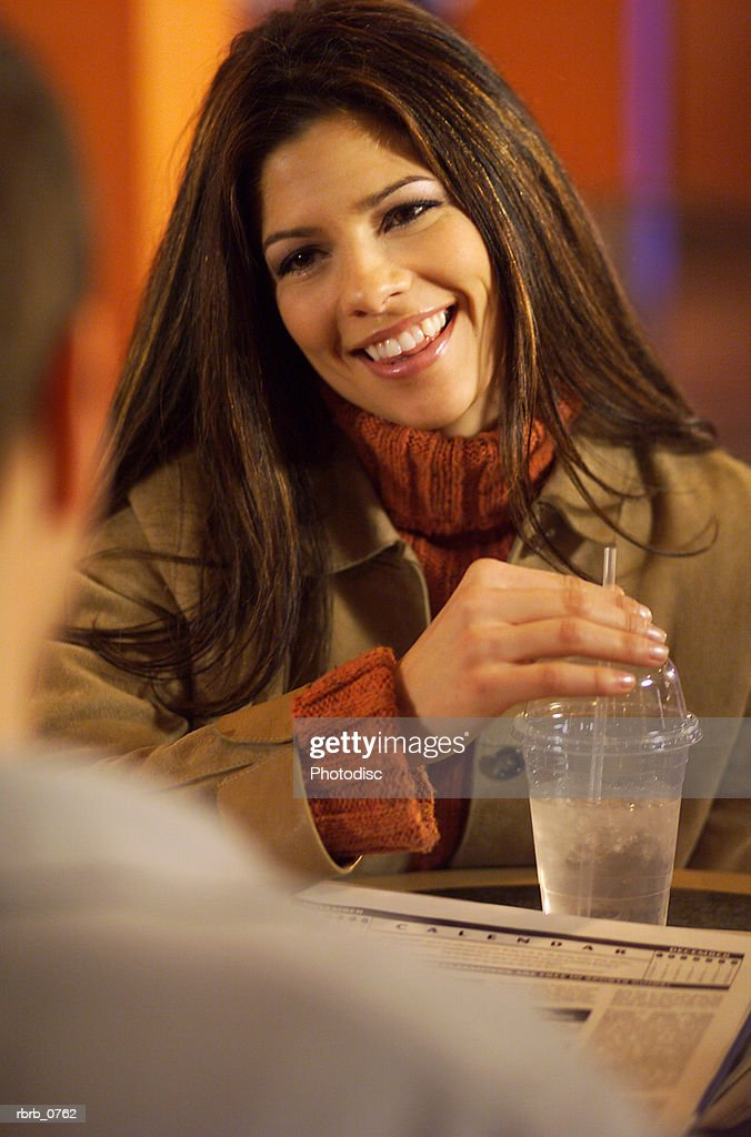 over the shoulder lifestyle portrait of an attractive young caucasian woman as she sits in a cafe and smiles : Stockfoto