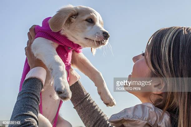Over the shoulder low angle view of young woman holding up puppy smiling