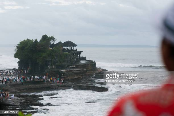 over the shoulder of a tourist in a red shirt, looking at the seaside temples of tanah lot, a famous tourist attraction in bali, indonesia - christine wehrmeier stock photos and pictures