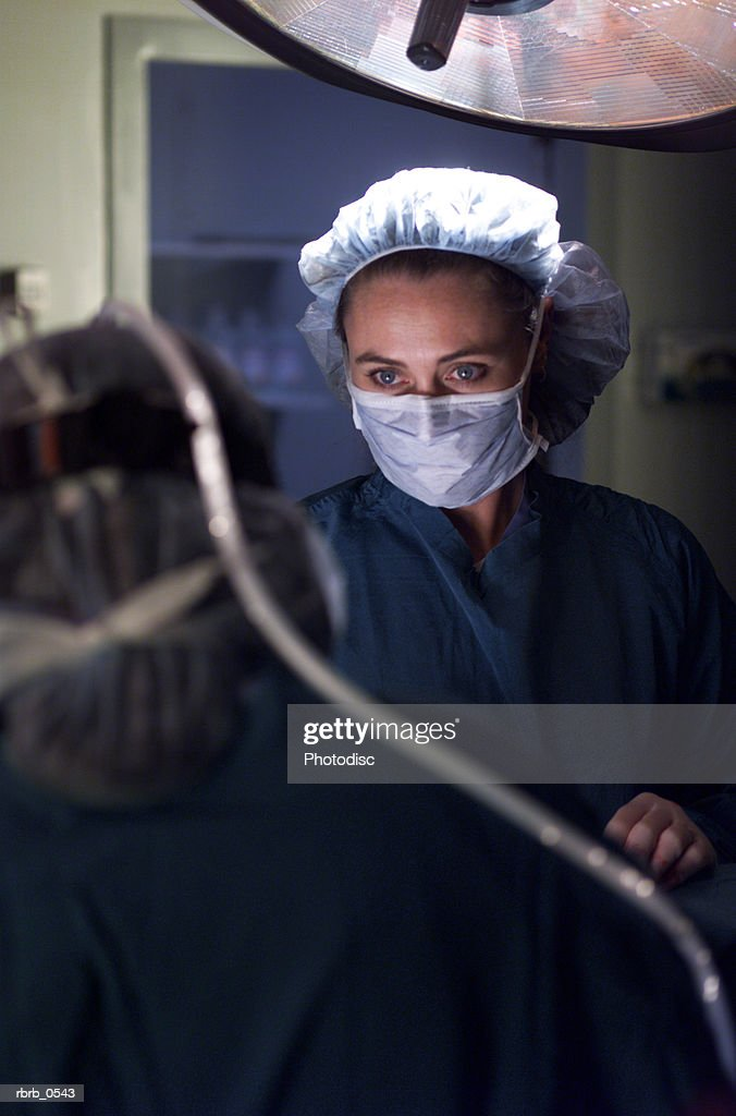 over the shoulder shot of a nurse in an operating room as she works on a patient : Stockfoto