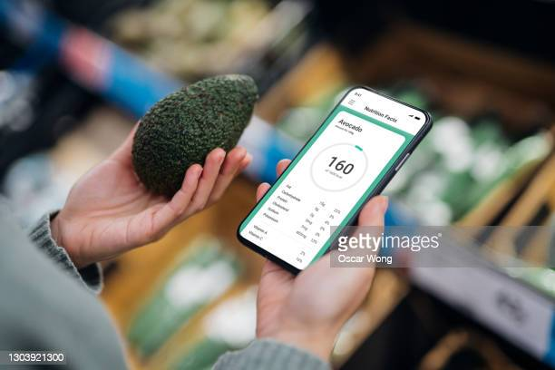 over the shoulder shot of woman using mobile app to track nutrition and count calories of an avocado with smartphone. - vitality stock pictures, royalty-free photos & images