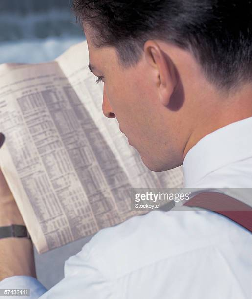 over the shoulder view of a businessman reading the papers