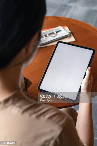 over de schouder weergave van een digitale tablet met een leeg scherm in de handen van een onherkenbare zakenvrouw (kopieerruimte) - looking over shoulder stockfoto's en -beelden
