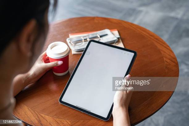 over the shoulder view of a digital tablet with a blank screen in the hands of an unrecognizable businesswoman (copy space) - copy space imagens e fotografias de stock